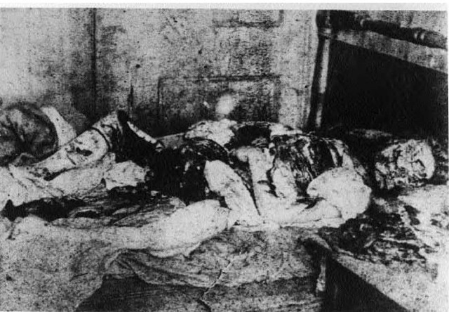 The body of Mary Jane Kelly lying on her bed on the afternoon of 9 November 1888. Parts of her body have been placed between her legs, under her head, and on the table, which can be seen at bottom right. Close scrutiny reveals marks on the wall above Mary's left hand that look like the letter M. Some writers have claimed that this clue was deliberately placed in this awkward position as a clue to James Maybrick being the murderer.