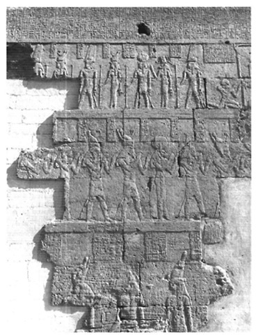 Relief in the Umm 'Ubaydah temple, Siwa Oasis: processions of gods and King Wenamen wearing the Libyan chief's ostrich feather headdress and kneeling in front of the shrine of Amen (top right)