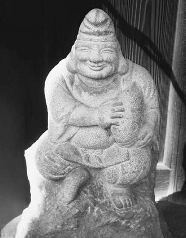 Stone image of the popular Japanese deity Ebisu, god of good fortune and protector of children, in a shrine at the Zuisen-ji Zen temple in Kamakura, Japan.