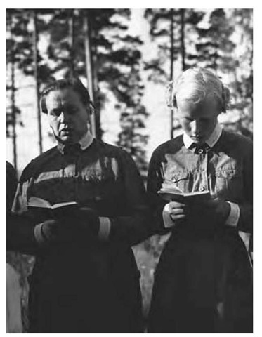 Two women of the Finnish Lotta Svard read from books, 1942. The purpose of the Lotta Svard, a volunteer organization made up of Finnish women, was to boost national morale and support the civil guard.