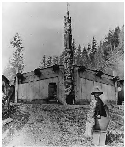 This Haida chief stands before a typical dwelling called the House Where the People Want to Go (1888). House names might reflect an attribute of the owner or relate to the construction or physical features of the house. Entry into the house was either through a hole in the bottom of a totem pole or through elliptical doorways cut into the front facade.