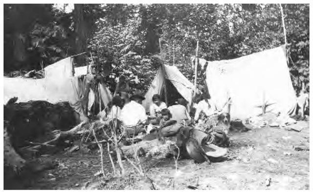 Westernmost Chilcotin Indians at breakfast at a temporary camp while visiting Bella Coola, British Columbia, in 1924.