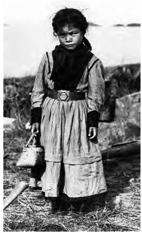 A small girl (Cree and Chipewyan) carries a birch-bark basket of blueberries (1914).