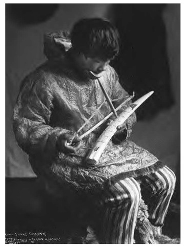 This ivory carver uses a bow to cause his wooden drill to burn into and penetrate a walrus tusk (1912).