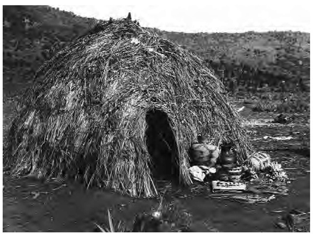 Most Western Apache lived in dome-shaped wickiups made of wood poles covered with bear grass. Outside this brush hut are Apache baskets. Other fine arts included cradle boards and pottery.
