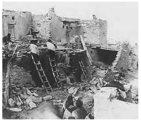 These Hopi women are shown building adobe houses. Distinctive one- or two-floor pueblo housing featured sandstone and adobe walls and roof beams of pine and juniper, gathered from afar. The dwellings were entered via ladders through openings in the roofs and were arranged around a central plaza.