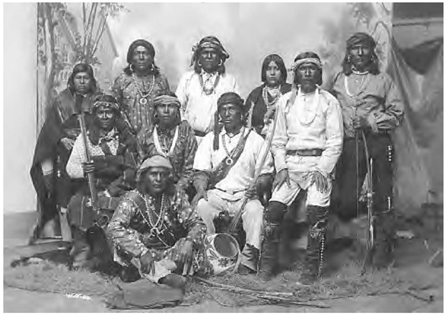 A group of Laguna men and women in the mid-1880s. The men wear cloth headbands, silver jewelry, cotton shirts, and trousers with woven belts, as well as leather leggings gartered at the knee. Two women wear dark wool mantas over cotton blouses and woven belts and blankets.