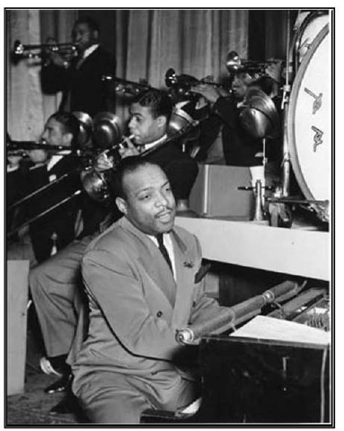 Count Basie playing with his orchestra.