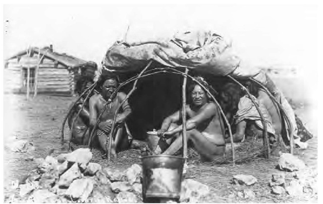 Religious activities among Dakota Indians included vision quests and ritual purification in the sweat lodge. These men are seated in a sweat lodge with its covering partially raised. Before the advent of tin buckets, water was carried in buffalo bladders into which hot stones were dropped.