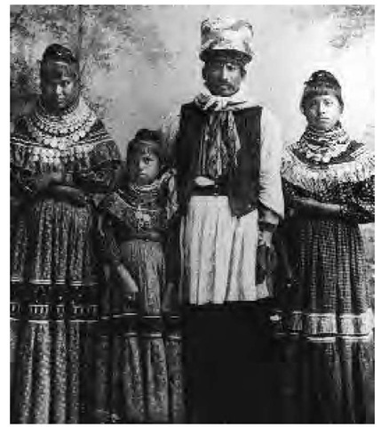 A Seminole family poses for a photographer. The women wear long skirts and many necklaces of beads and coins. The man wears a vest, a long shirt, and a tall turban fashionable among the nineteenth-century Seminole.