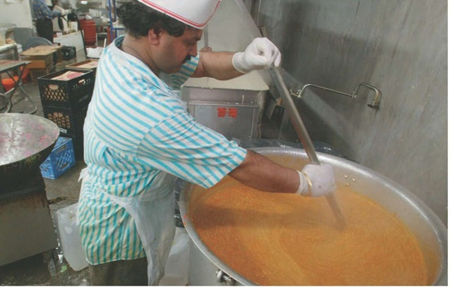 A cook stirs a large pot of mashed vegetables to be used to make pav bhaji, a popular Indian fast-food dish.