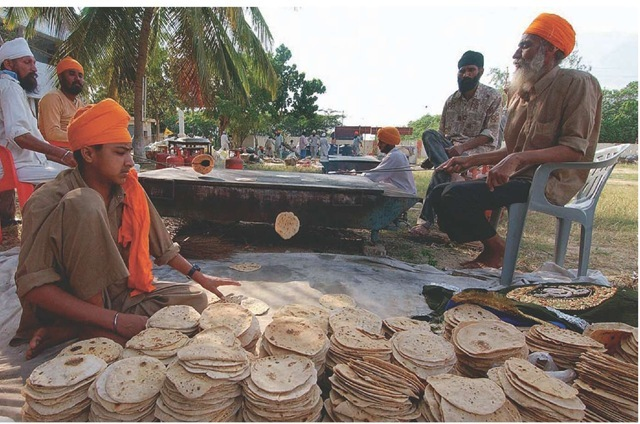 Indian flat breads called rotis cook on a hot griddle outdoors.