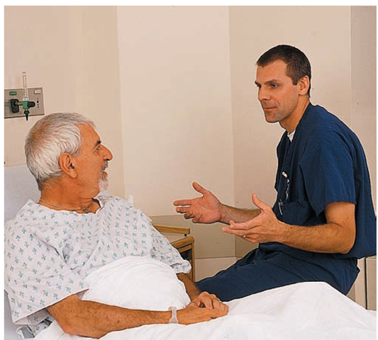 This nurse uses principles of therapeutic communication when interacting with his client. He uses appropriate positioning (eye level), does not invade the client's personal space, makes appropriate eye contact, and generally mirrors the client's body position. He speaks and then carefully listens to what the client has to say.